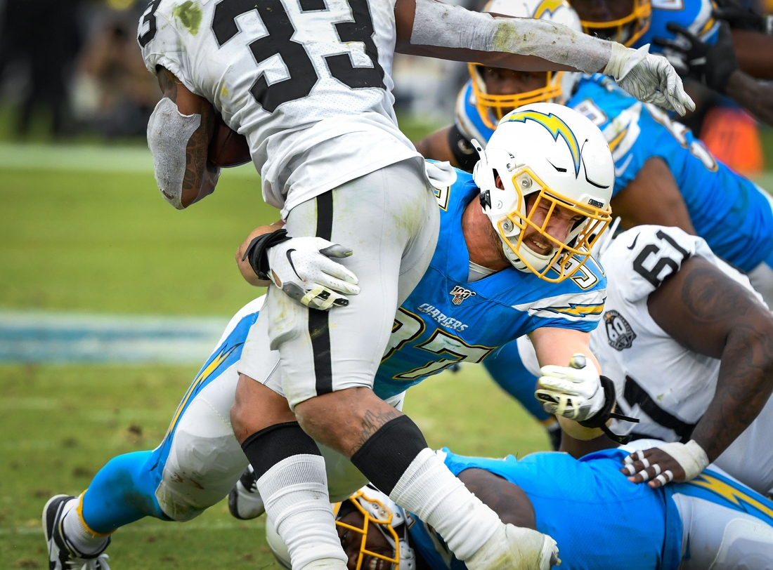 Dec 22, 2019; Carson, California, USA; Los Angeles Chargers defensive end Joey Bosa (97) stops Oakland Raiders running back DeAndre Washington (33) during the fourth quarter at Dignity Health Sports Park. Mandatory Credit: Robert Hanashiro-USA TODAY Sports