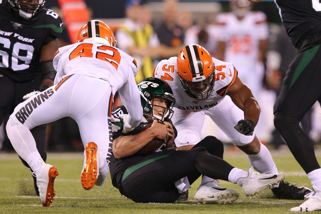 Sep 16, 2019; East Rutherford, NJ, USA; New York Jets quarterback Trevor Siemian (19) is sacked by Cleveland Browns safety Morgan Burnett (42) and defensive end Olivier Vernon (54) during the second quarter at MetLife Stadium. Mandatory Credit: Brad Penner-USA TODAY Sports