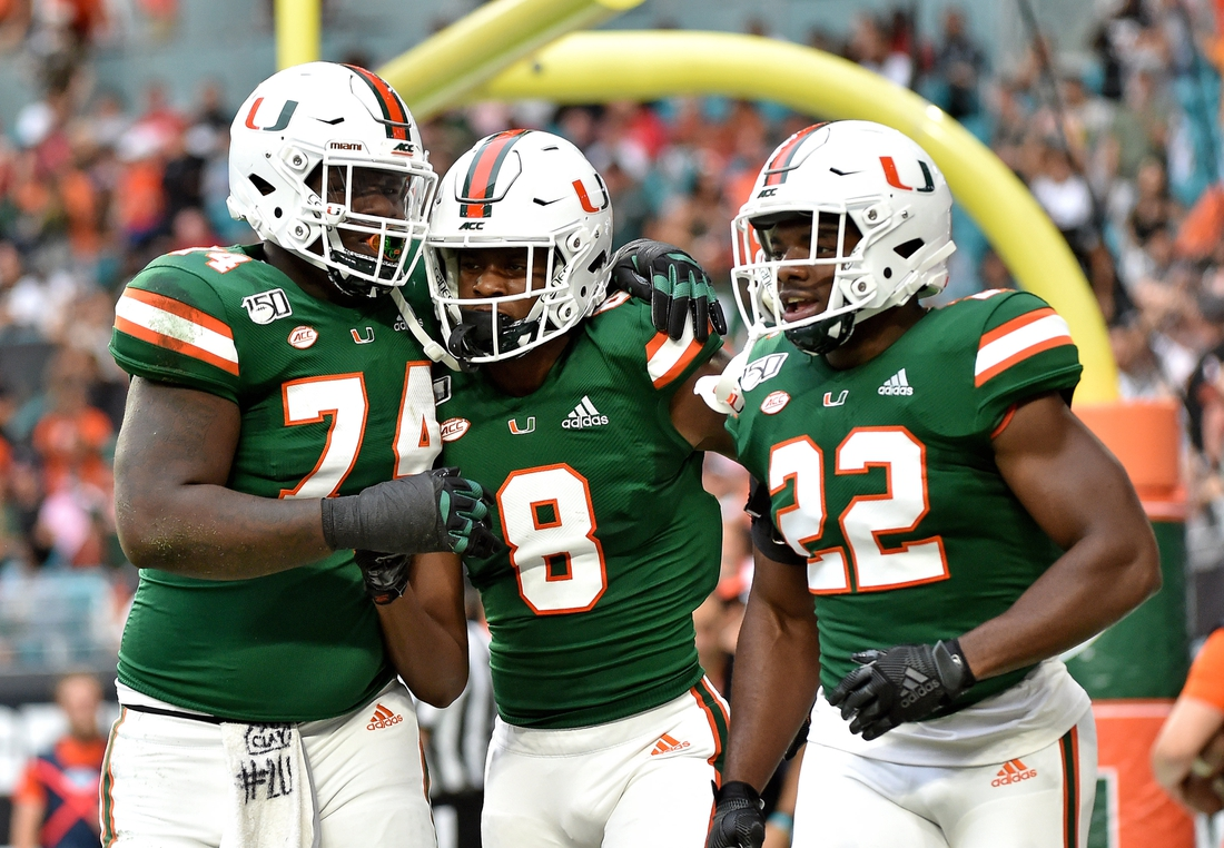 Nov 9, 2019; Miami Gardens, FL, USA; Miami Hurricanes wide receiver Dee Wiggins (center) celebrates with offensive lineman John Campbell Jr. (left) and running back Robert Burns (right) after scoring a touchdown against the Louisville Cardinals during the first half at Hard Rock Stadium. Mandatory Credit: Steve Mitchell-USA TODAY Sports