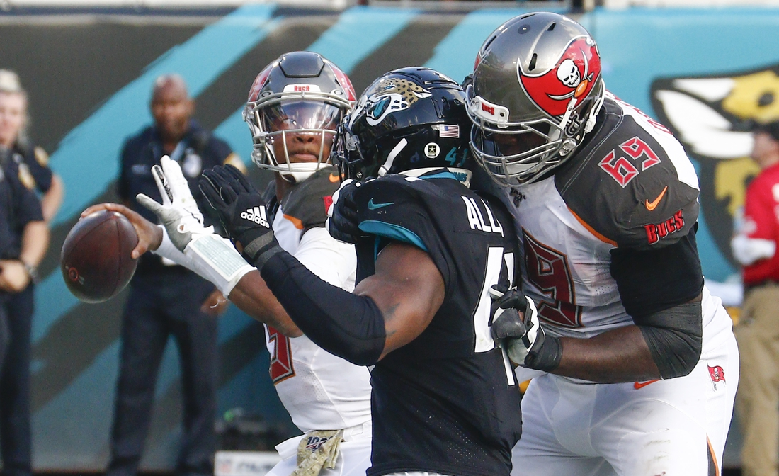 Dec 1, 2019; Jacksonville, FL, USA;  Tampa Bay Buccaneers offensive tackle Demar Dotson (69) blocks Jacksonville Jaguars defensive end Josh Allen (41) as Buccaneers quarterback Jameis Winston (left) throws a pass during the second half at TIAA Bank Field. Mandatory Credit: Reinhold Matay-USA TODAY Sports