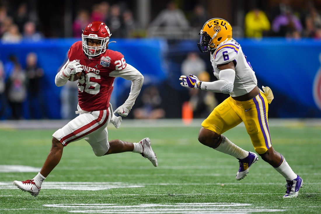 Dec 28, 2019; Atlanta, Georgia, USA; Oklahoma Sooners running back Kennedy Brooks (26) runs the ball as LSU Tigers linebacker Jacob Phillips (6) defends during the second quarter of the 2019 Peach Bowl college football playoff semifinal game at Mercedes-Benz Stadium. Mandatory Credit: Dale Zanine-USA TODAY Sports