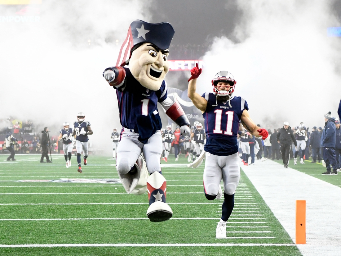 Jan 4, 2020; Foxborough, Massachusetts, USA;  New England Patriots wide receiver Julian Edelman (11) and Pat the Patriot  run onto the field before a game against the Tennessee Titans at Gillette Stadium. Mandatory Credit: Brian Fluharty-USA TODAY Sports