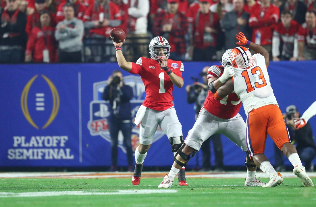 Dec 28, 2019; Glendale, AZ, USA; Ohio State Buckeyes quarterback Justin Fields (1) throws a pass against Clemson Tigers defensive tackle Tyler Davis (13) during the first quarter in the 2019 Fiesta Bowl college football playoff semifinal game at State Farm Stadium. Mandatory Credit: Mark J. Rebilas-USA TODAY Sports