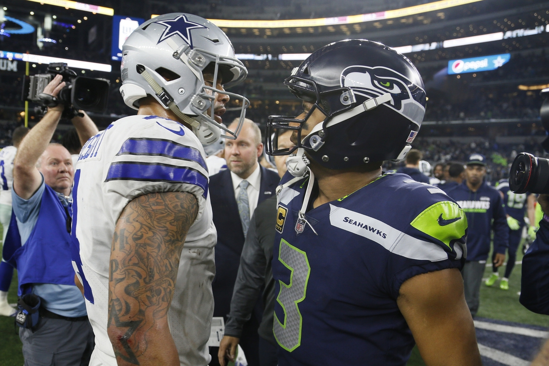 Dec 24, 2017; Arlington, TX, USA; Dallas Cowboys quarterback Dak Prescott (4) meets with Seattle Seahawks quarterback Russell Wilson (3) after a game at AT&T Stadium. Mandatory Credit: Tim Heitman-USA TODAY Sports