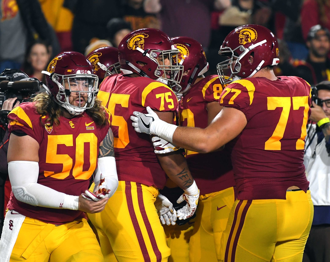Nov 10, 2018; Los Angeles, CA, USA; USC Trojans center Toa Lobendahn (50), guard Chris Brown (77), and guard Alijah Vera-Tucker (75) celebrate after a touchdown in the second quarter of the game against the California Golden Bears  at the Los Angeles Memorial Coliseum. Mandatory Credit: Jayne Kamin-Oncea-USA TODAY Sports