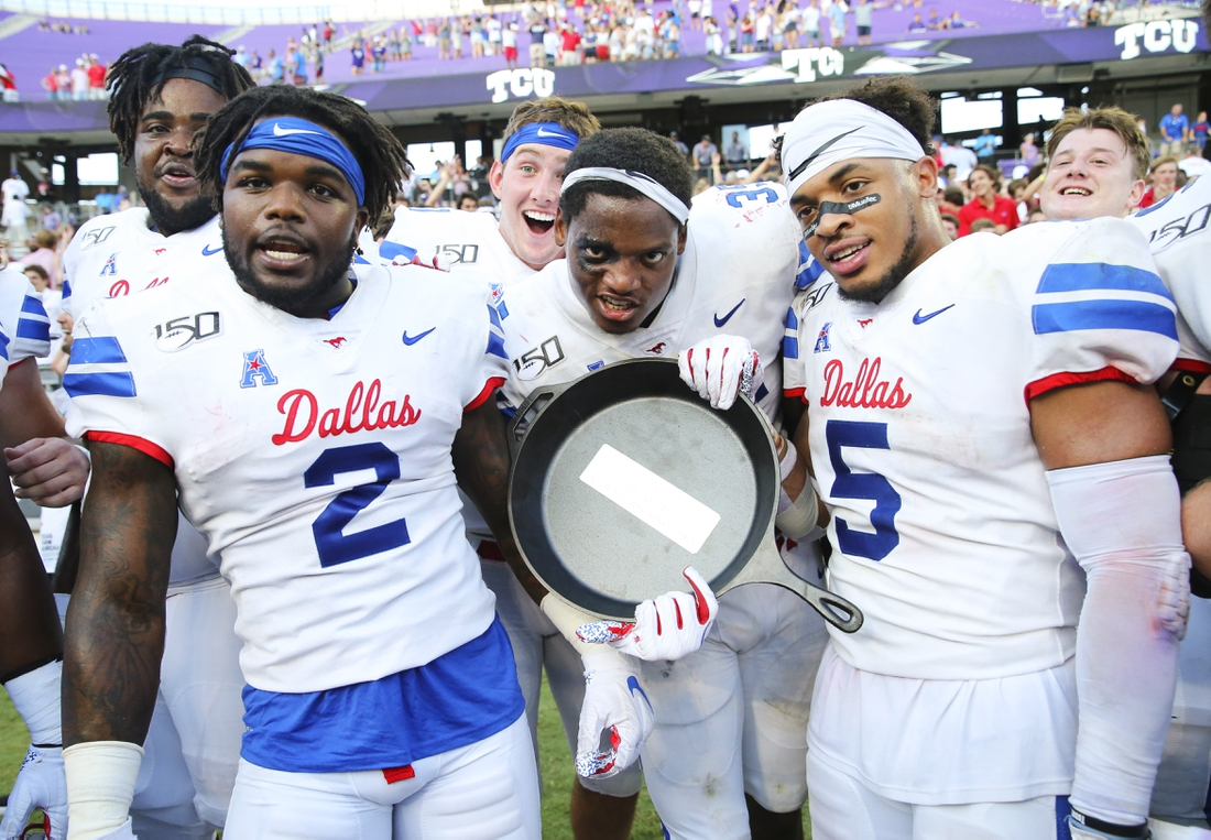 Sep 21, 2019; Fort Worth, TX, USA; Southern Methodist Mustangs players celebrate with the Iron Skillet after the victory against the TCU Horned Frogs at Amon G. Carter Stadium. Mandatory Credit: Kevin Jairaj-USA TODAY Sports