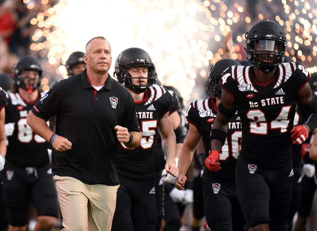 Sep 21, 2019; Raleigh, NC, USA; North Carolina State Wolfpack head coach Dave Doeren (left) leads his team onto the field prior to a game against the Ball State Cardinals at Carter-Finley Stadium. Mandatory Credit: Rob Kinnan-USA TODAY Sports