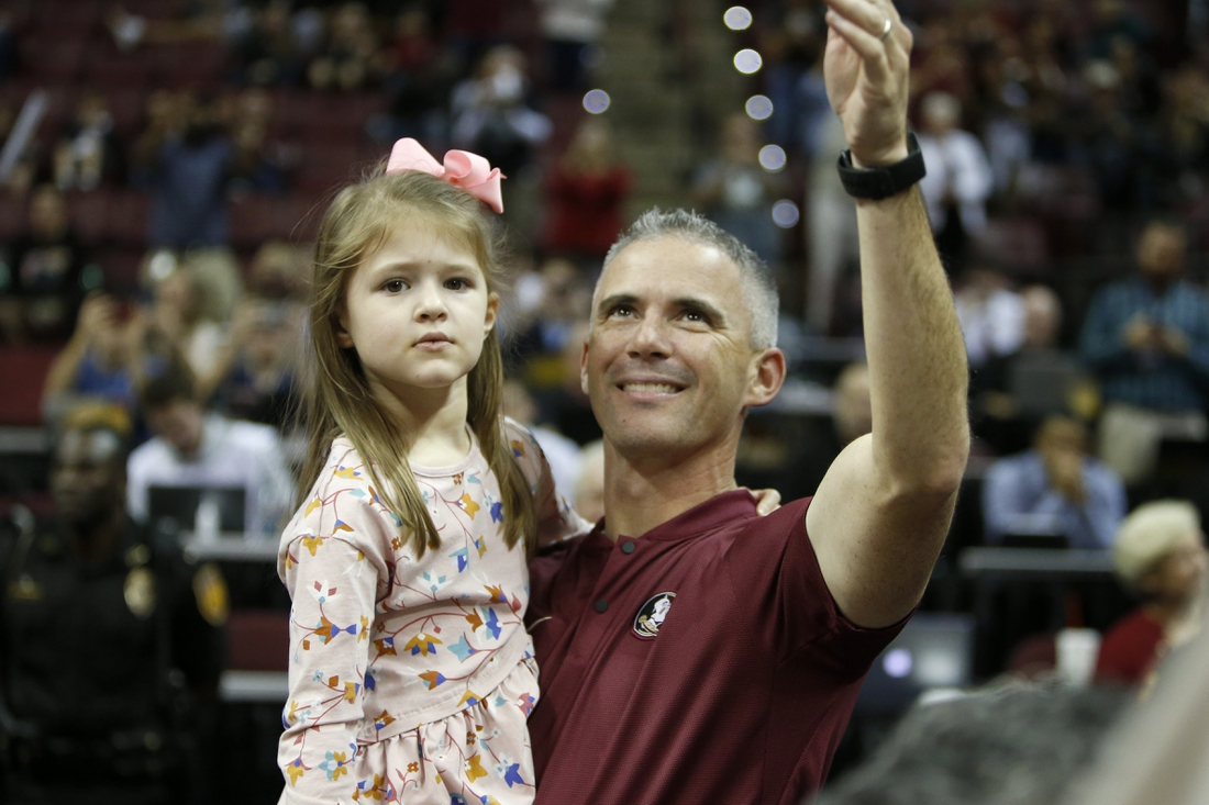 Dec 8, 2019; Tallahassee, FL, USA; The new Florida State Seminoles head football coach Mike Norvell waves to the crowd with his daughter Mila while being introduced during a stoppage in play against the Clemson Tigers at the Donald L. Tucker Center. Mandatory Credit: Glenn Beil-USA TODAY Sports