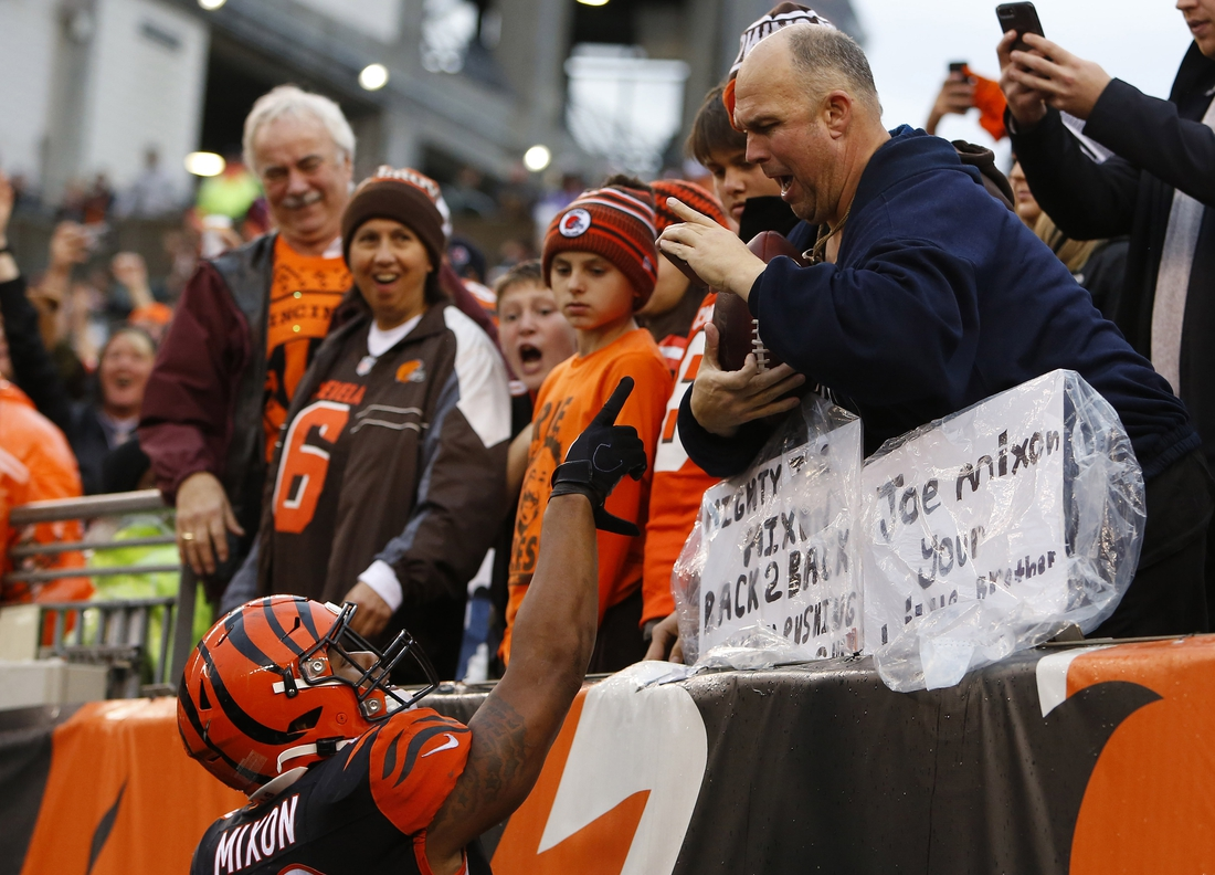 Dec 29, 2019; Cincinnati, Ohio, USA; Cincinnati Bengals running back Joe Mixon (28) hands a fan a football after scoring a touchdown against the Cleveland Browns during the second half at Paul Brown Stadium. Mandatory Credit: David Kohl-USA TODAY Sports