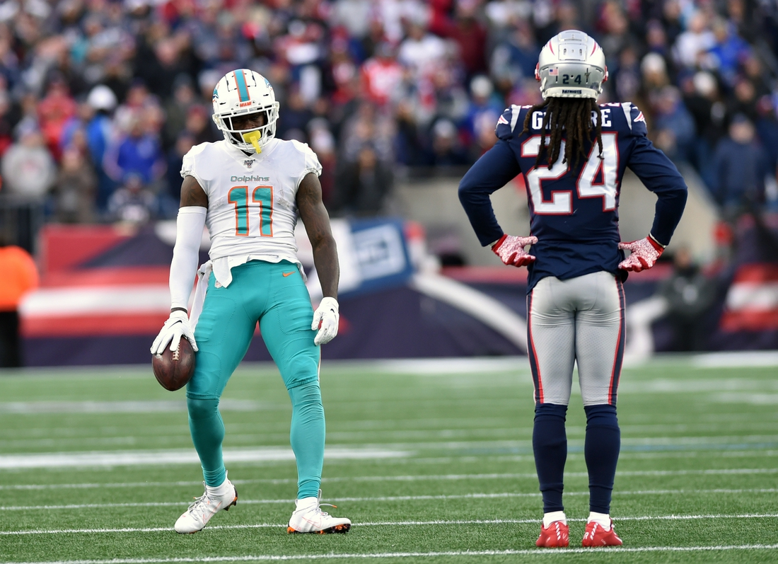 Dec 29, 2019; Foxborough, Massachusetts, USA;  Miami Dolphins wide receiver DeVante Parker (11) reacts in front of New England Patriots cornerback Stephon Gilmore (24) after making a catch for a first down during the second half at Gillette Stadium. Mandatory Credit: Bob DeChiara-USA TODAY Sports