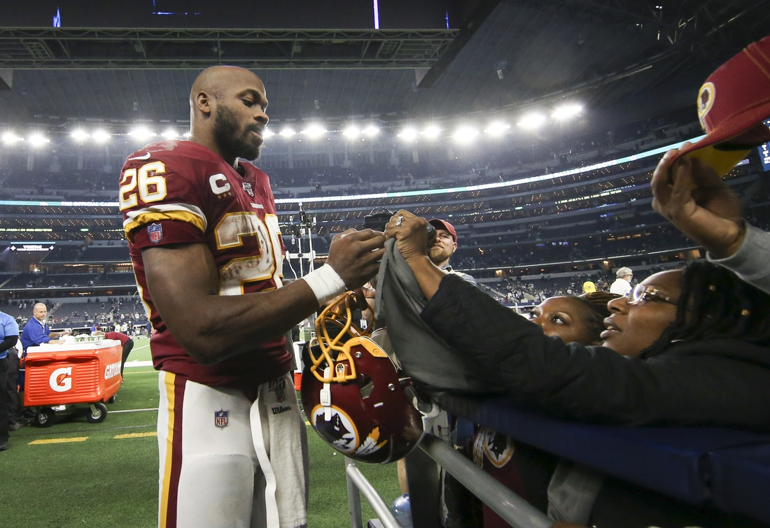 Dec 29, 2019; Arlington, Texas, USA;   Washington Redskins running back Adrian Peterson (26) signs autographs after the game against the Dallas Cowboys at AT&T Stadium. Mandatory Credit: Kevin Jairaj-USA TODAY Sports