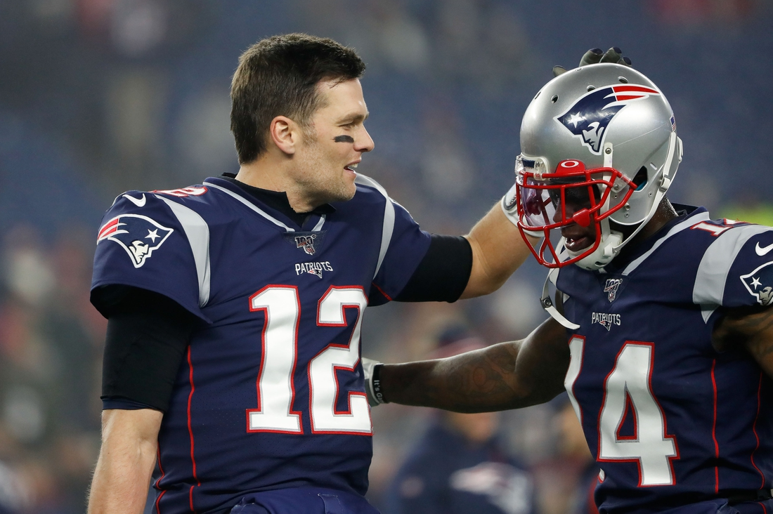 Jan 4, 2020; Foxborough, Massachusetts, USA;  New England Patriots quarterback Tom Brady (12) high-fives wide receiver Mohamed Sanu (14) before a game against the Tennessee Titans at Gillette Stadium. Mandatory Credit: Winslow Townson-USA TODAY Sports