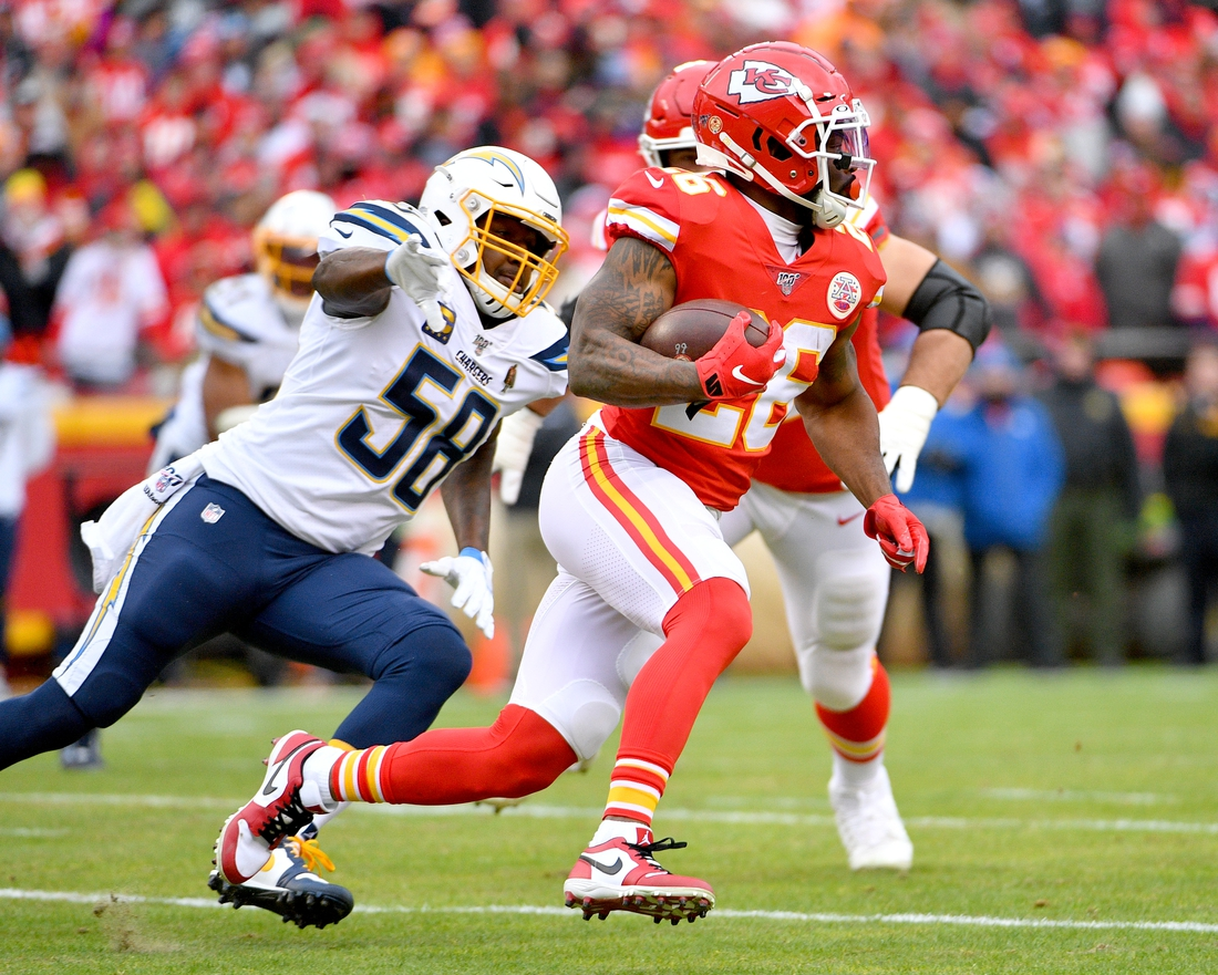 Dec 29, 2019; Kansas City, Missouri, USA; Kansas City Chiefs running back Damien Williams (26) runs the ball as Los Angeles Chargers outside linebacker Thomas Davis (58) attempts the tackle during the game at Arrowhead Stadium. Mandatory Credit: Denny Medley-USA TODAY Sports