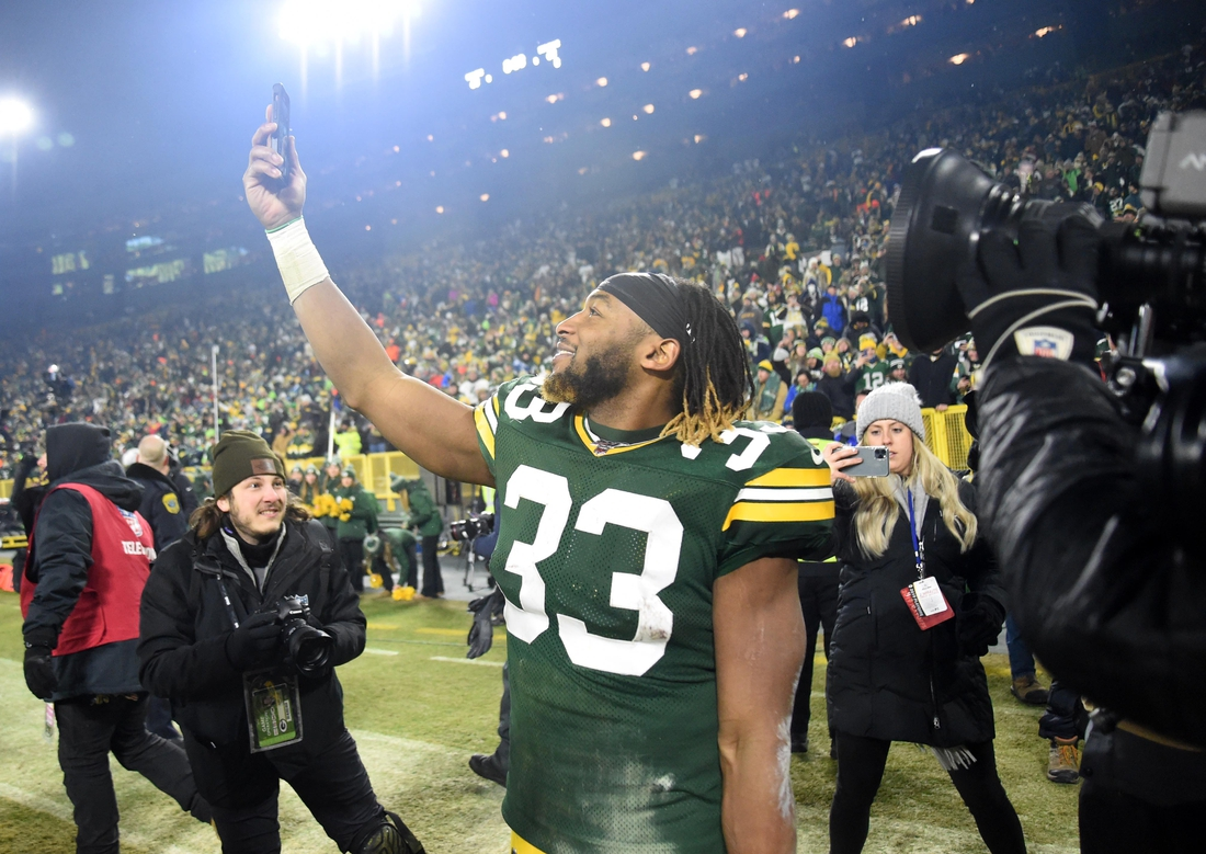 Jan 12, 2020; Green Bay, WI, USA;  Green Bay Packers running back Aaron Jones (33) uses a cell phone as he leaves the field after defeating the Seattle Seahawks in a NFC Divisional Round playoff football game at Lambeau Field. Mandatory Credit: Benny Sieu-USA TODAY Sports