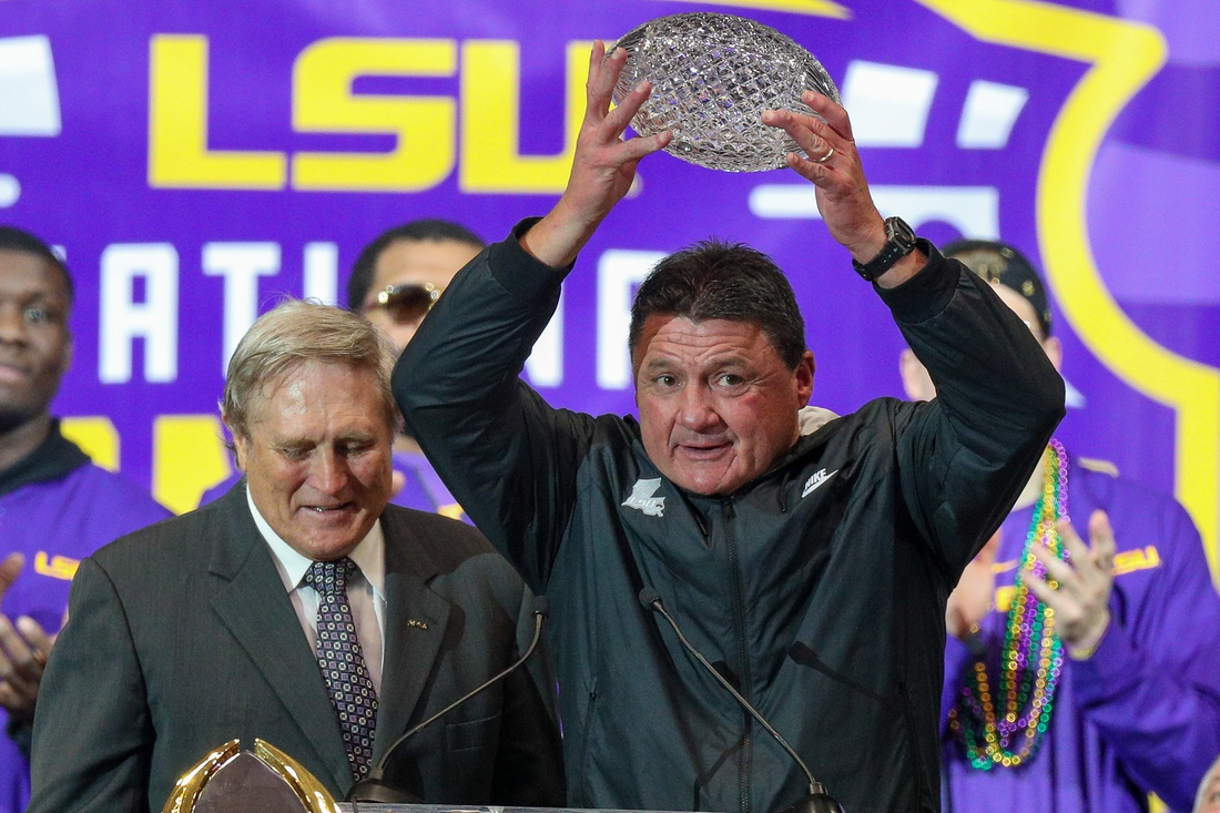 Jan 18, 2020; Baton Rouge, Louisiana, USA; AFCA Coaches  Trophy presented by Amway is presented by Gary Darnell (left) and Gary Mongolian (right) to LSU Tigers head coach Ed Orgeron during the LSU championship trophy presentation at Pete Maravich Assembly Center. Mandatory Credit: Stephen Lew-USA TODAY Sports