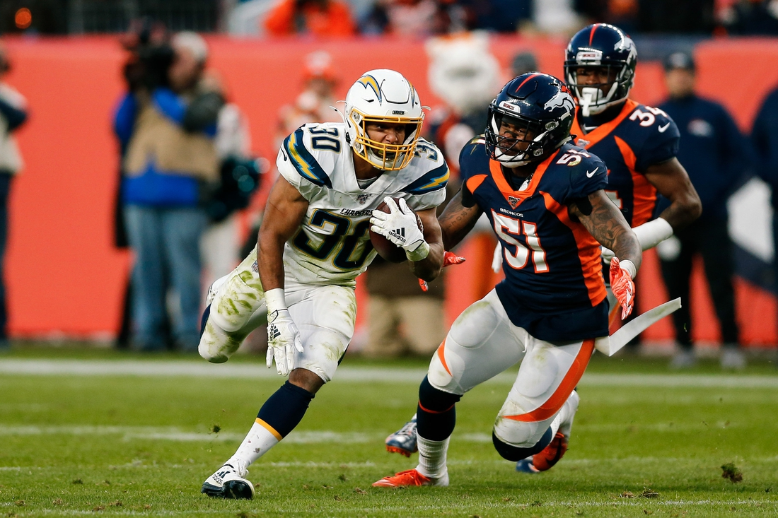 Dec 1, 2019; Denver, CO, USA; Los Angeles Chargers running back Austin Ekeler (30) runs the ball ahead of Denver Broncos inside linebacker Todd Davis (51) in the third quarter at Empower Field at Mile High. Mandatory Credit: Isaiah J. Downing-USA TODAY Sports