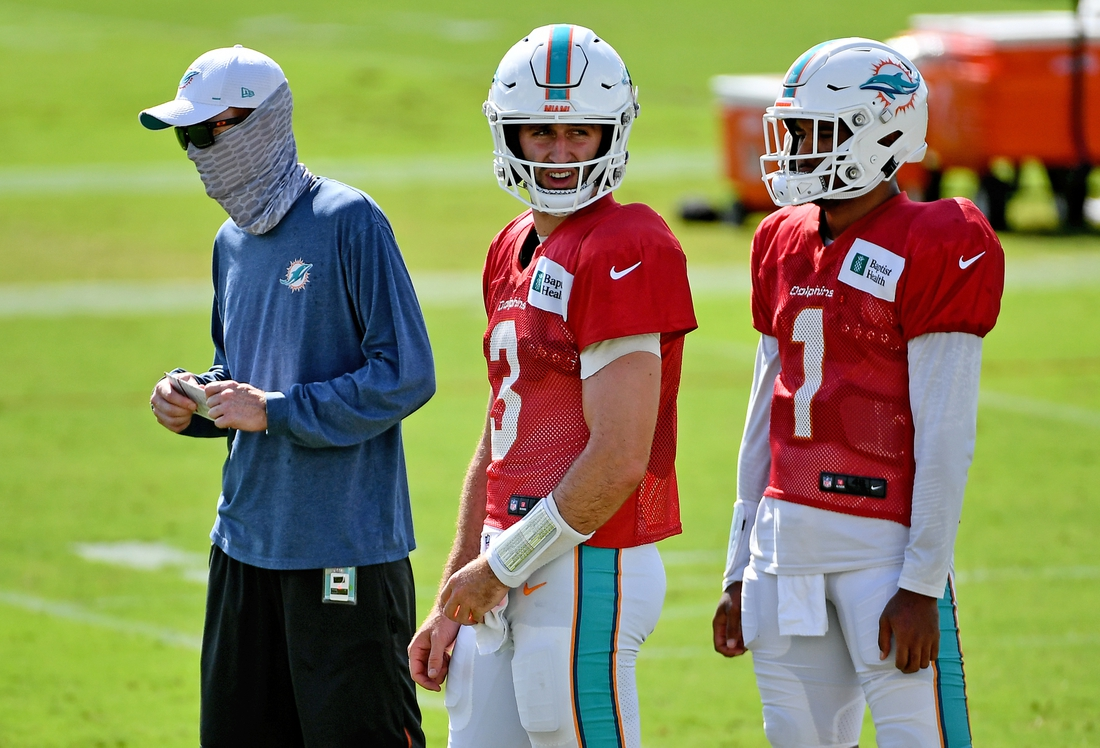 Sep 1, 2020; Miami Gardens, Florida, USA; Miami Dolphins quarterback Josh Rosen (3) and quarterback Tua Tagovailoa (1) stand with quarterbacks coach Robby Brown (L) during training camp at Baptist Health Training Facility. Mandatory Credit: Jasen Vinlove-USA TODAY Sports