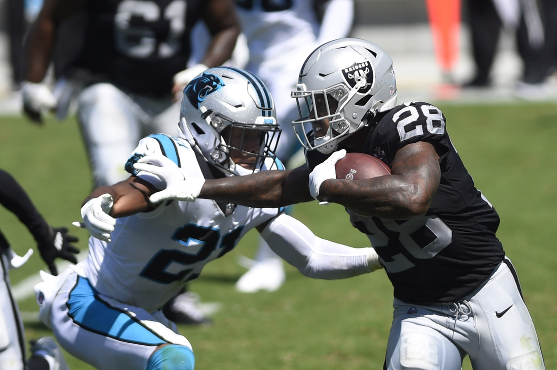 Sep 13, 2020; Charlotte, North Carolina, USA;  Las Vegas Raiders running back Josh Jacobs (28) with the ball as Carolina Panthers safety Jeremy Chinn (21) defends in the second quarter at Bank of America Stadium. Mandatory Credit: Bob Donnan-USA TODAY Sports