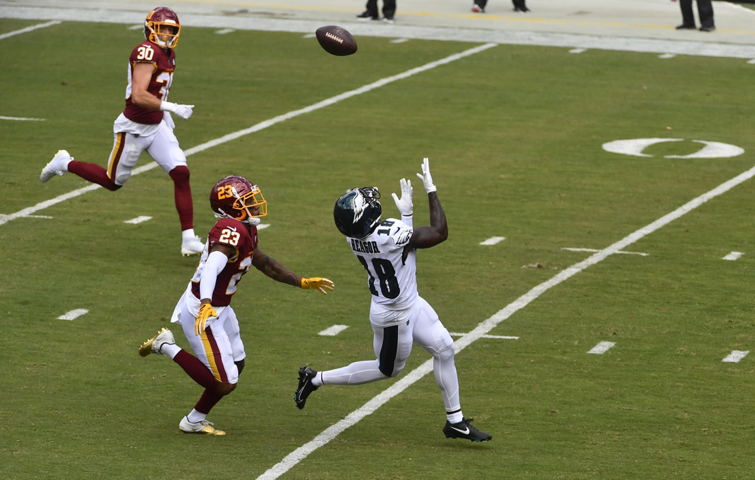 Sep 13, 2020; Landover, Maryland, USA; Philadelphia Eagles wide receiver Jalen Reagor (18) makes a catch as Washington Football Team cornerback Ronald Darby (23) chases during the first half quarter at FedExField. Mandatory Credit: Brad Mills-USA TODAY Sports