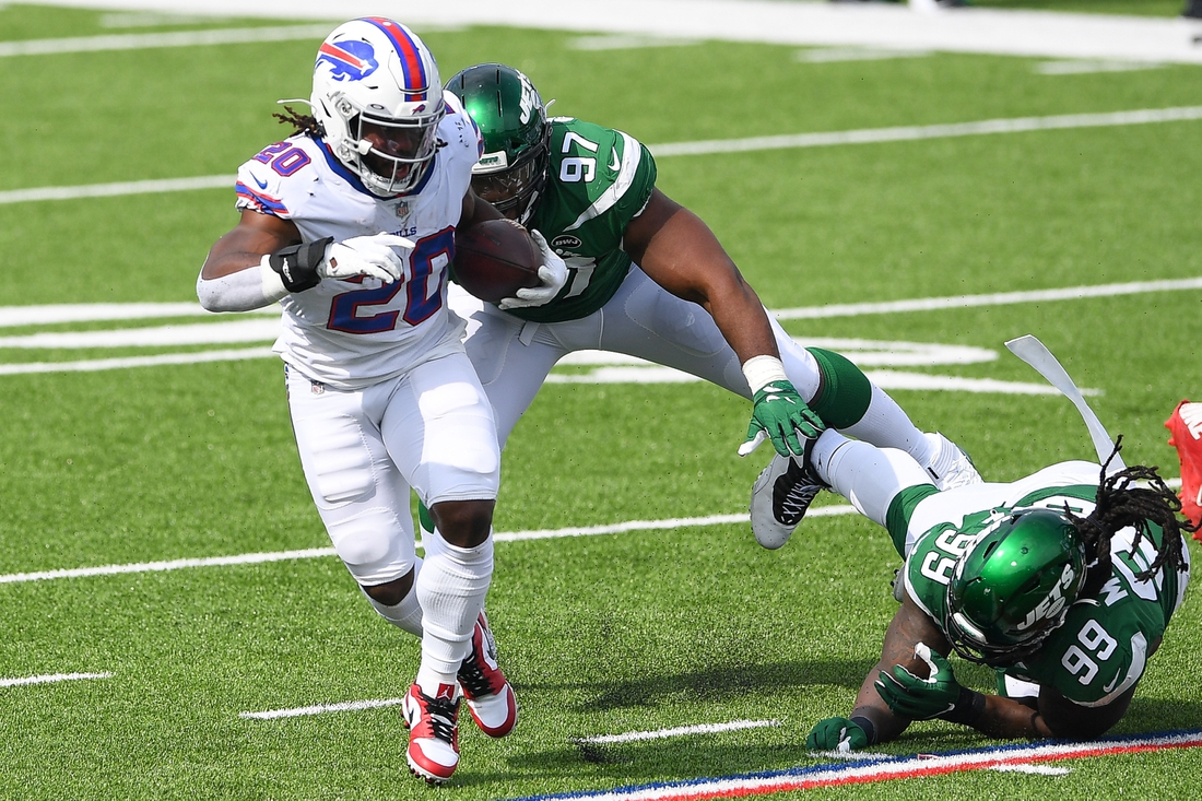 Sep 13, 2020; Orchard Park, New York, USA; Buffalo Bills running back Zack Moss (20) runs with the ball in front of New York Jets defensive tackles Nathan Shepherd (97) and Steve McLendon (99) during the third quarter at Bills Stadium. Mandatory Credit: Rich Barnes-USA TODAY Sports
