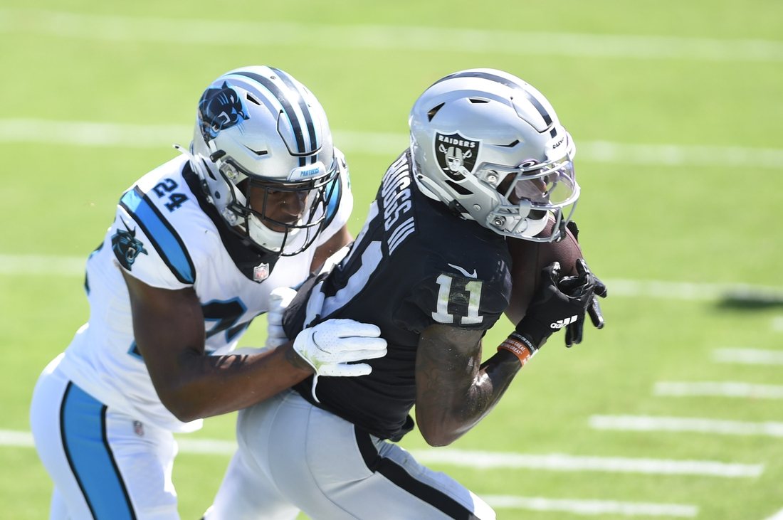 Sep 13, 2020; Charlotte, North Carolina, USA;  Las Vegas Raiders wide receiver Henry Ruggs III (11) tries to make a catch as Carolina Panthers cornerback Rasul Douglas (24) defends in the second quarter at Bank of America Stadium. Mandatory Credit: Bob Donnan-USA TODAY Sports