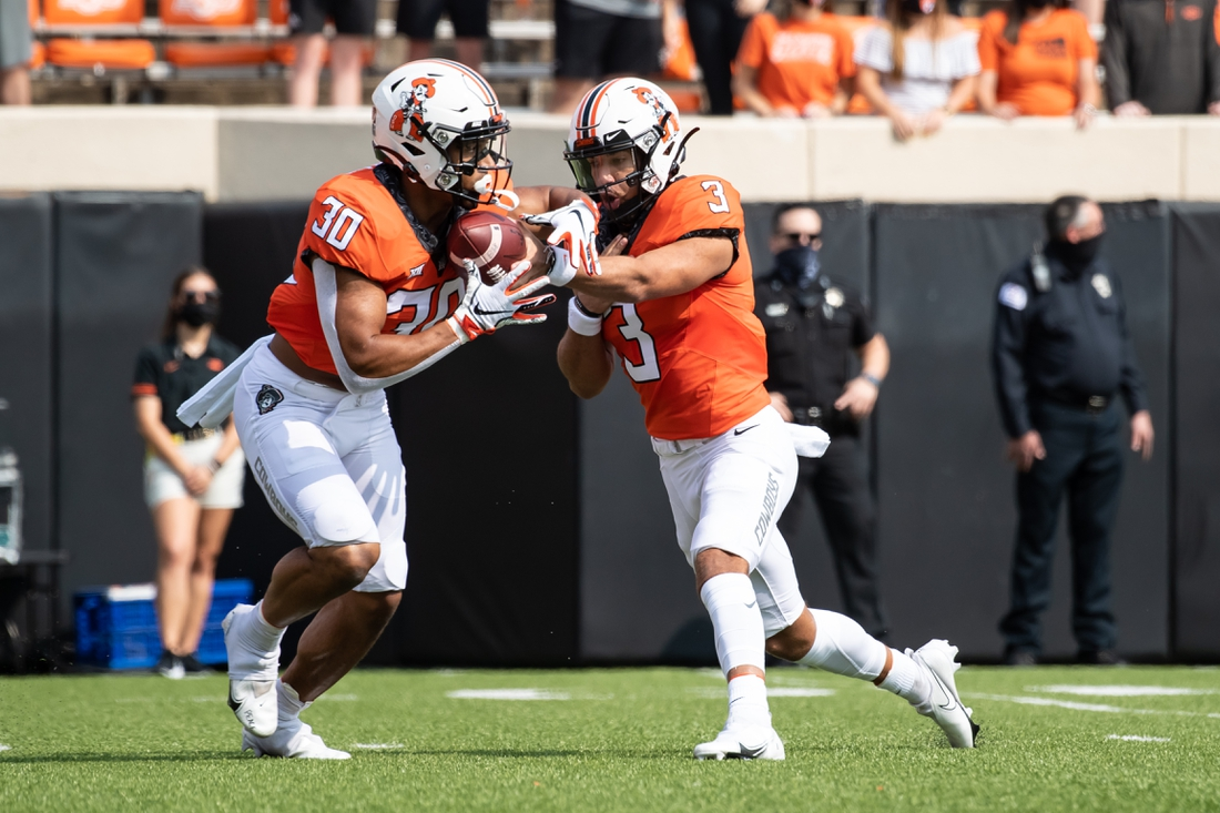 Sep 19, 2020; Stillwater, Oklahoma, USA; Oklahoma State Cowboys quarterback Spencer Sanders (3) hands off to   running back Chuba Hubbard (30) against the Tulsa Golden Hurricane during the first half at Boone Pickens Stadium. Mandatory Credit: Rob Ferguson-USA TODAY Sports