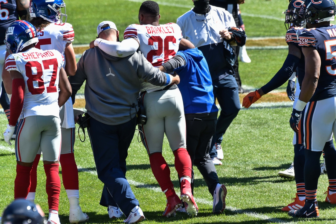 Sep 20, 2020; Chicago, Illinois, USA; New York Giants running back Saquon Barkley (26) is helped off the field after suffering an injury during the second quarter against the Chicago Bears at Soldier Field. Mandatory Credit: Jeffrey Becker-USA TODAY Sports