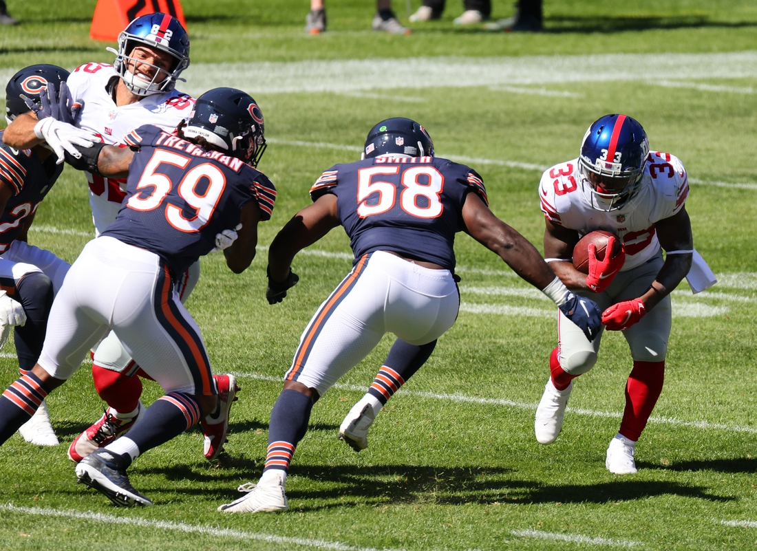 Sep 20, 2020; Chicago, Illinois, USA; New York Giants running back Dion Lewis (33) rushes the ball against Chicago Bears inside linebacker Roquan Smith (58) during the second quarter at Soldier Field. Mandatory Credit: Mike Dinovo-USA TODAY Sports