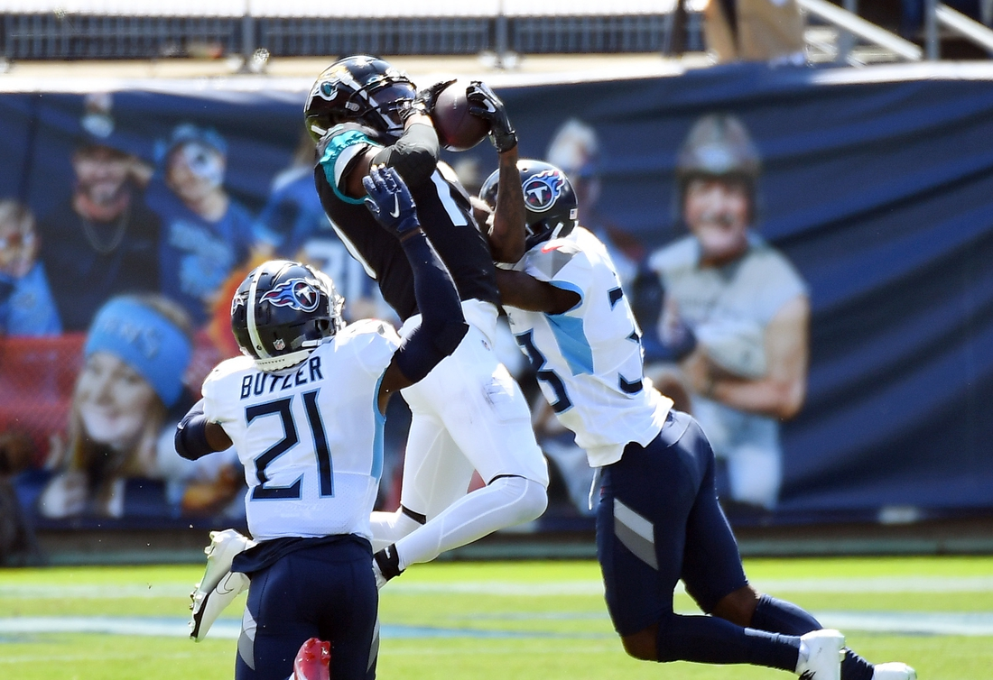 Sep 20, 2020; Nashville, Tennessee, USA; Jacksonville Jaguars wide receiver D.J. Chark (17) catches a pass in coverage from Tennessee Titans cornerback Malcolm Butler (21) and Tennessee Titans cornerback Johnathan Joseph (33) during the first half at Nissan Stadium. Mandatory Credit: Christopher Hanewinckel-USA TODAY Sports