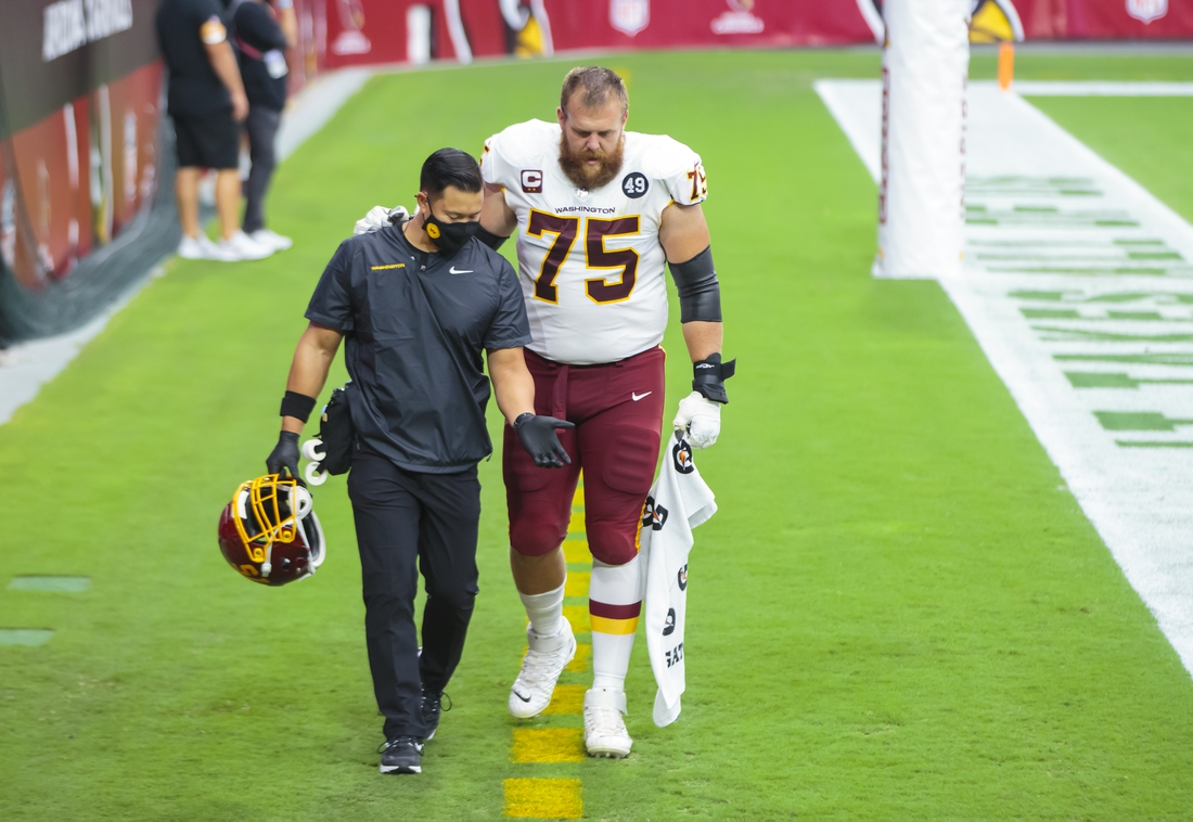Sep 20, 2020; Glendale, Arizona, USA; Washington Football Team guard Brandon Scherff (75) is helped off the field to the locker room by a trainer after suffering an injury against the Arizona Cardinals at State Farm Stadium. Mandatory Credit: Mark J. Rebilas-USA TODAY Sports