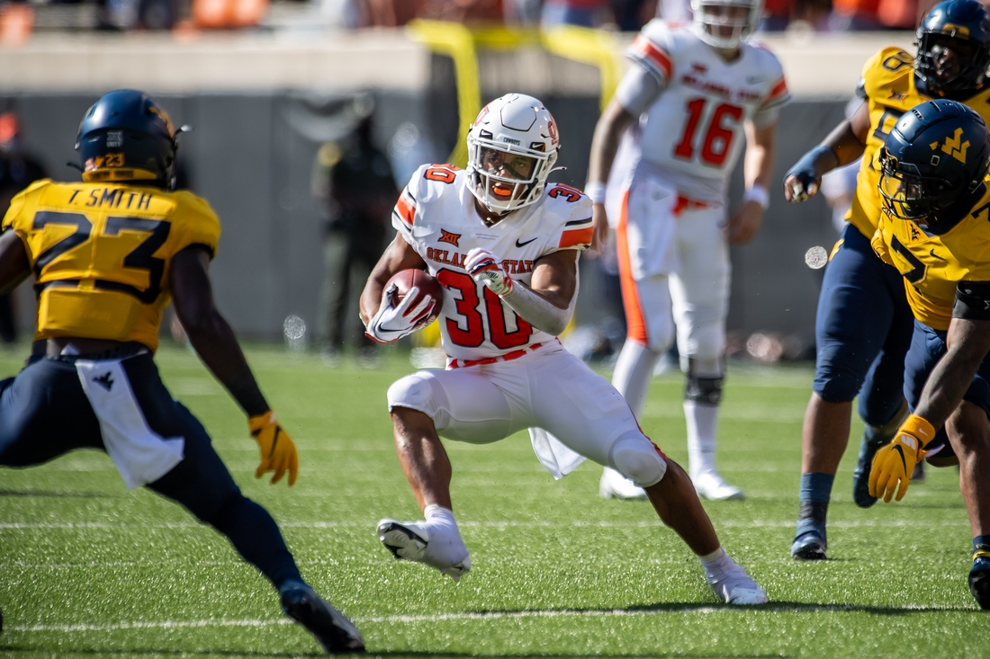 Sep 26, 2020; Stillwater, Oklahoma, USA; Oklahoma State Cowboys running back Chuba Hubbard (30) runs the ball against West Virginia Mountaineers punter Tykee Smith (23) during the first half at Boone Pickens Stadium. Mandatory Credit: Rob Ferguson-USA TODAY Sports