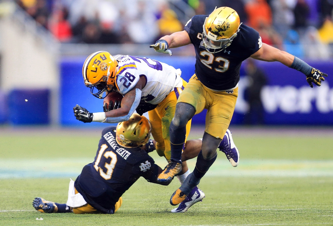 Jan 1, 2018; Orlando, FL, USA; Notre Dame Fighting Irish linebacker Drue Tranquill (23) and safety Jordan Genmark-Heath (13) tackle LSU Tigers running back Darrel Williams (28) during the second half in the 2018 Citrus Bowl at Camping World Stadium. Mandatory Credit: Matt Stamey-USA TODAY Sports