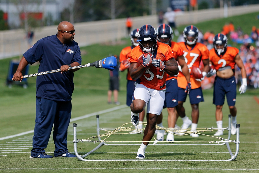 Jul 28, 2018; Englewood, CO, USA; Denver Broncos running backs coach Curtis Modkins (L) pokes for the ball as running back De'Angelo Henderson Sr. (33) runs through the ropes on the first day of training camp at UCHealth Training Center. Mandatory Credit: Isaiah J. Downing-USA TODAY Sports