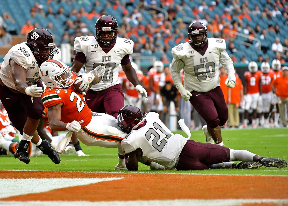 Sep 14, 2019; Miami Gardens, FL, USA; Miami Hurricanes running back Cam'Ron Harris (23) scores a touchdown against Bethune Cookman Wildcats safety Tydarius Peters (21) during the second half at Hard Rock Stadium. Mandatory Credit: Steve Mitchell-USA TODAY Sports
