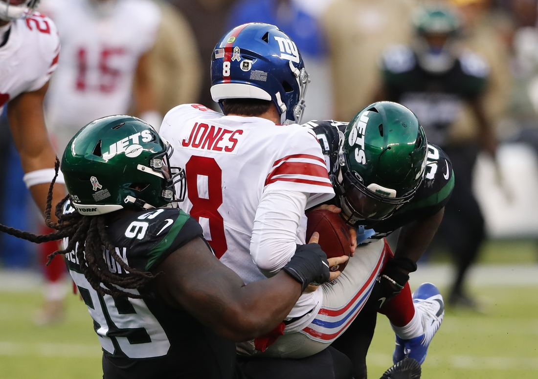 Nov 10, 2019; East Rutherford, NJ, USA;  New York Giants quarterback Daniel Jones (8) is sacked by New York Jets nose tackle Steve McLendon (99) and outside linebacker James Burgess (58) during the second half at MetLife Stadium. Mandatory Credit: Noah K. Murray-USA TODAY Sports