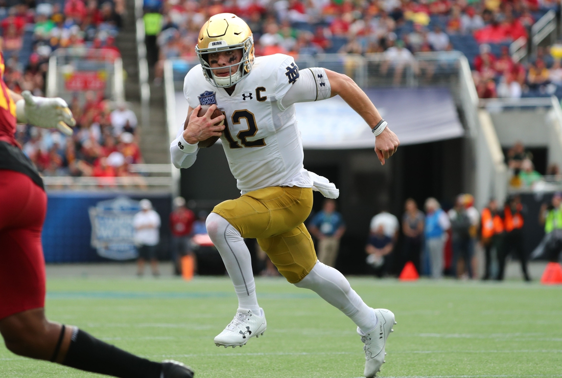 Dec 28, 2019; Orlando, Florida, USA; Notre Dame Fighting Irish quarterback Ian Book (12) runs with the ball against the Iowa State Cyclones during the second half at Camping World Stadium. Mandatory Credit: Kim Klement-USA TODAY Sports