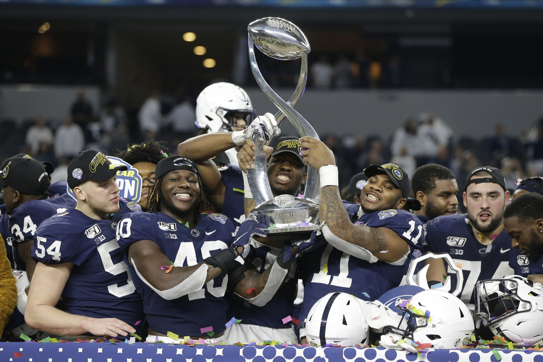 Dec 28, 2019; Arlington, Texas, USA; Penn State Nittany Lions linebacker Micah Parsons (11) and linebacker Jesse Luketa (40) hold up the trophy after the game against the Memphis Tigers at AT&T Stadium. Mandatory Credit: Tim Heitman-USA TODAY Sports