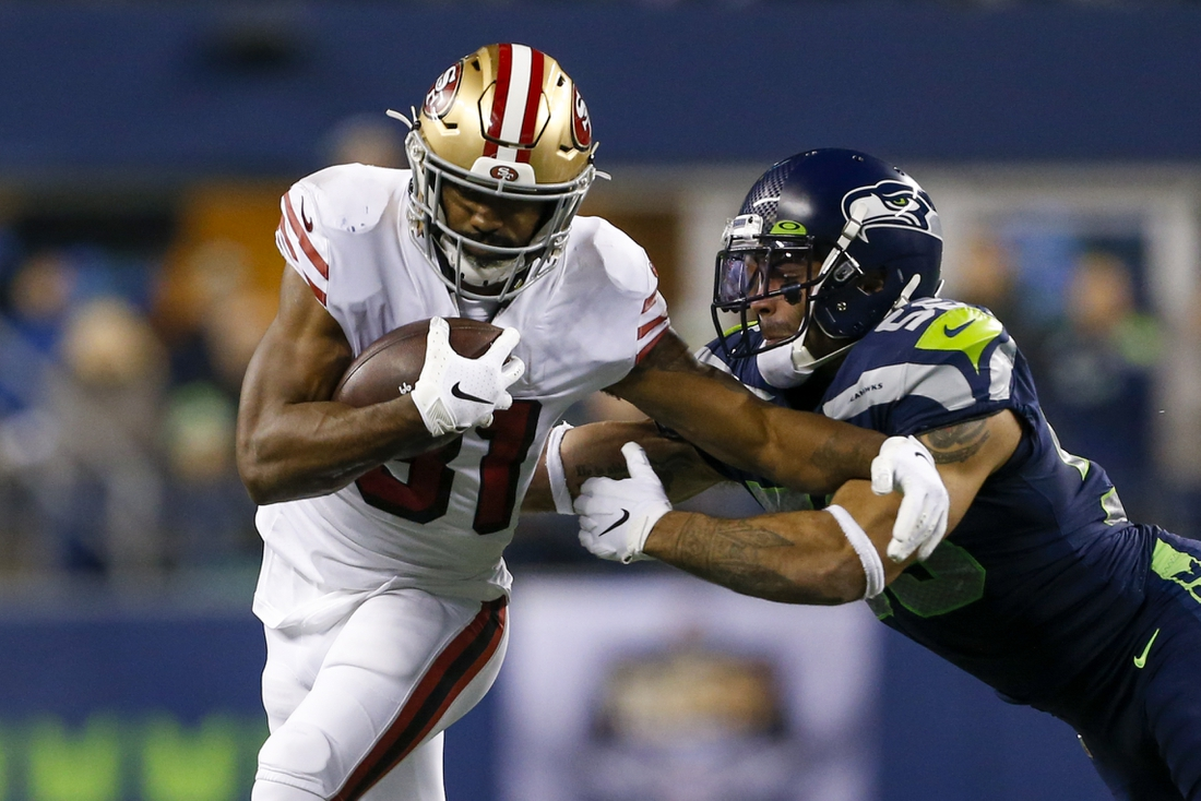 Dec 29, 2019; Seattle, Washington, USA; San Francisco 49ers running back Raheem Mostert (31) breaks a tackle attempt by Seattle Seahawks linebacker Mychal Kendricks (56) during the first quarter at CenturyLink Field. Mandatory Credit: Joe Nicholson-USA TODAY Sports
