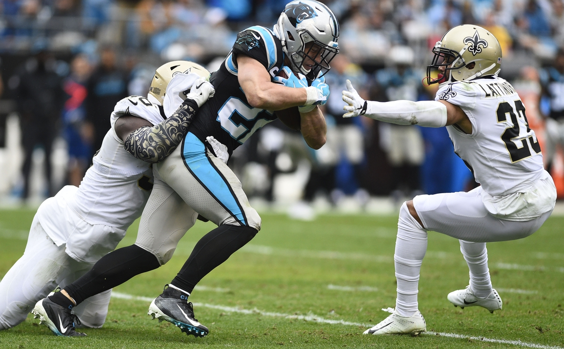 Dec 29, 2019; Charlotte, North Carolina, USA; Carolina Panthers running back Christian McCaffrey (22) is tackled by New Orleans Saints outside linebacker Demario Davis (56) and cornerback Marshon Lattimore (23) in the second quarter at Bank of America Stadium. Mandatory Credit: Bob Donnan-USA TODAY Sports
