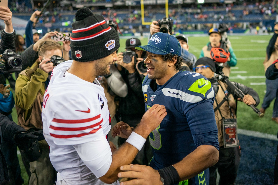 December 29, 2019; Seattle, Washington, USA; San Francisco 49ers quarterback Jimmy Garoppolo (10, left) talks to Seattle Seahawks quarterback Russell Wilson (3, right) after the game at CenturyLink Field. Mandatory Credit: Kyle Terada-USA TODAY Sports