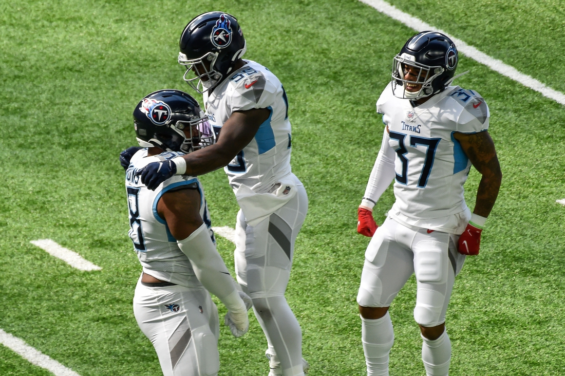 Sep 27, 2020; Minneapolis, Minnesota, USA; Tennessee Titans defensive tackle Jeffery Simmons (left) and inside linebacker Jayon Brown (middle) celebrate a sack by Simmons as safety Amani Hooker (37) looks on against the Minnesota Vikings during the first quarter at U.S. Bank Stadium. Mandatory Credit: Jeffrey Becker-USA TODAY Sports