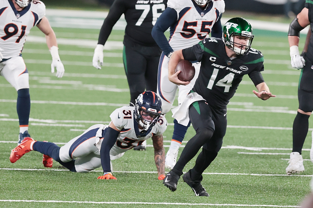Oct 1, 2020; East Rutherford, New Jersey, USA; New York Jets quarterback Sam Darnold (14) breaks a tackle by Denver Broncos free safety Justin Simmons (31) for a touchdown at MetLife Stadium. Mandatory Credit: Vincent Carchietta-USA TODAY Sports