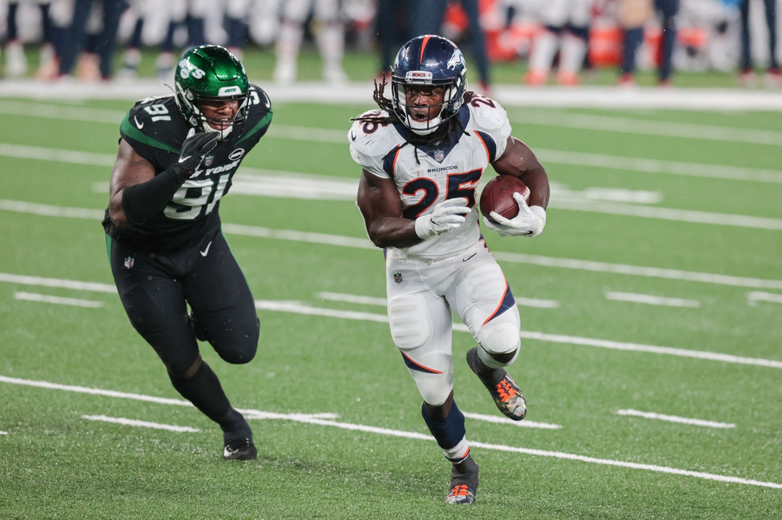 Oct 1, 2020; East Rutherford, New Jersey, USA; Denver Broncos running back Melvin Gordon (25) carries the ball as New York Jets defensive end John Franklin-Myers (91) pursues during the second half at MetLife Stadium. Mandatory Credit: Vincent Carchietta-USA TODAY Sports