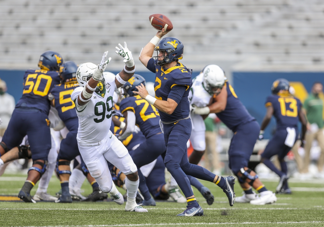 Oct 3, 2020; Morgantown, West Virginia, USA; West Virginia Mountaineers quarterback Jarret Doege (2) throws a pass and is pressured by Baylor Bears linebacker William Bradley-King (99) during the first quarter at Mountaineer Field at Milan Puskar Stadium. Mandatory Credit: Ben Queen-USA TODAY Sports