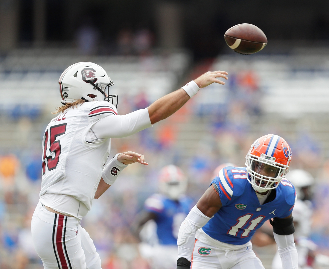 Oct 3, 2020; Gainesville, FL, USA;  South Carolina quarterback Collin Hill (15) throws the ball as the Florida Gators defense rushes in during a football game at Ben Hill Griffin Stadium, in Gainesville, Fla. Oct. 3, 2020.  Mandatory Credit: Brad McClenny-USA TODAY NETWORK