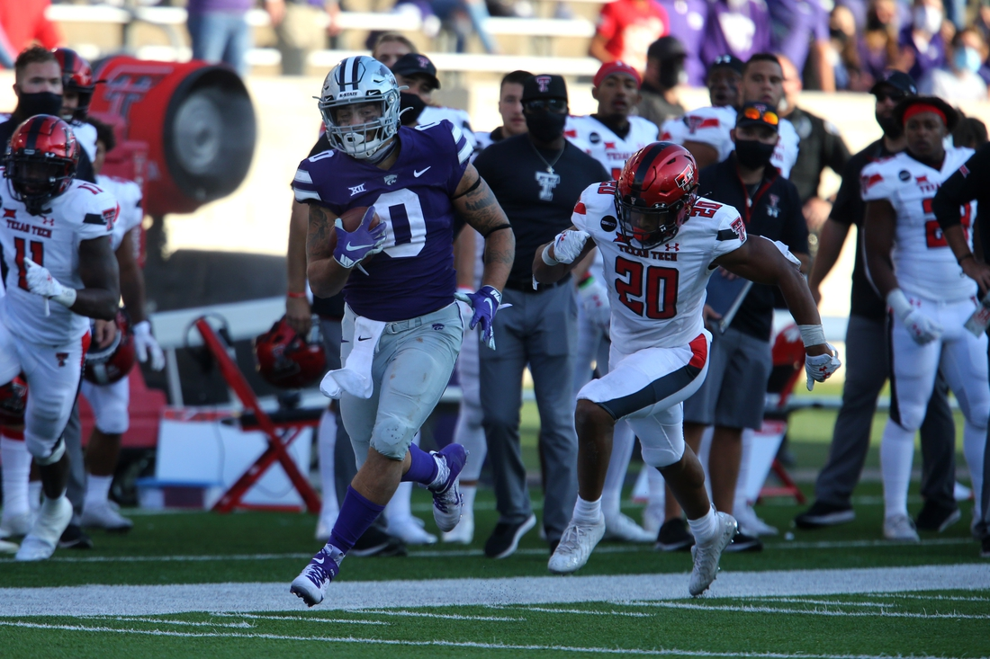Oct 3, 2020; Manhattan, Kansas, USA; Kansas State Wildcats tight end Briley Moore (0) runs past Texas Tech Red Raiders linebacker Kosi Eldridge (20) during a game at Bill Snyder Family Football Stadium. Mandatory Credit: Scott Sewell-USA TODAY Sports