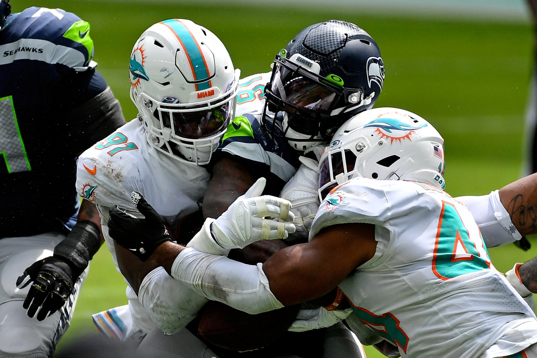 Oct 4, 2020; Miami Gardens, Florida, USA; Miami Dolphins outside linebacker Elandon Roberts (44) and defensive end Emmanuel Ogbah (91) tackle Seattle Seahawks running back Chris Carson (32)during the first half at Hard Rock Stadium. Mandatory Credit: Jasen Vinlove-USA TODAY Sports