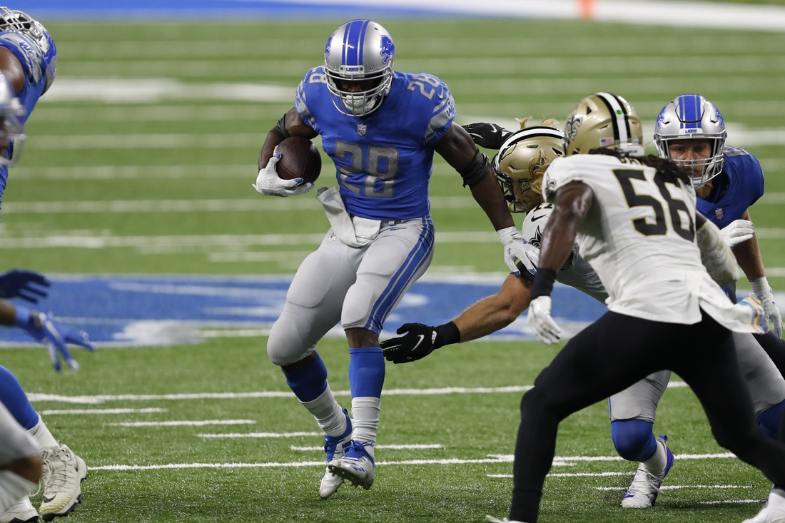 Oct 4, 2020; Detroit, Michigan, USA; Detroit Lions running back Adrian Peterson (28) runs the ball against New Orleans Saints middle linebacker Alex Anzalone (47) and outside linebacker Demario Davis (56) during the fourth quarter at Ford Field. Mandatory Credit: Raj Mehta-USA TODAY Sports
