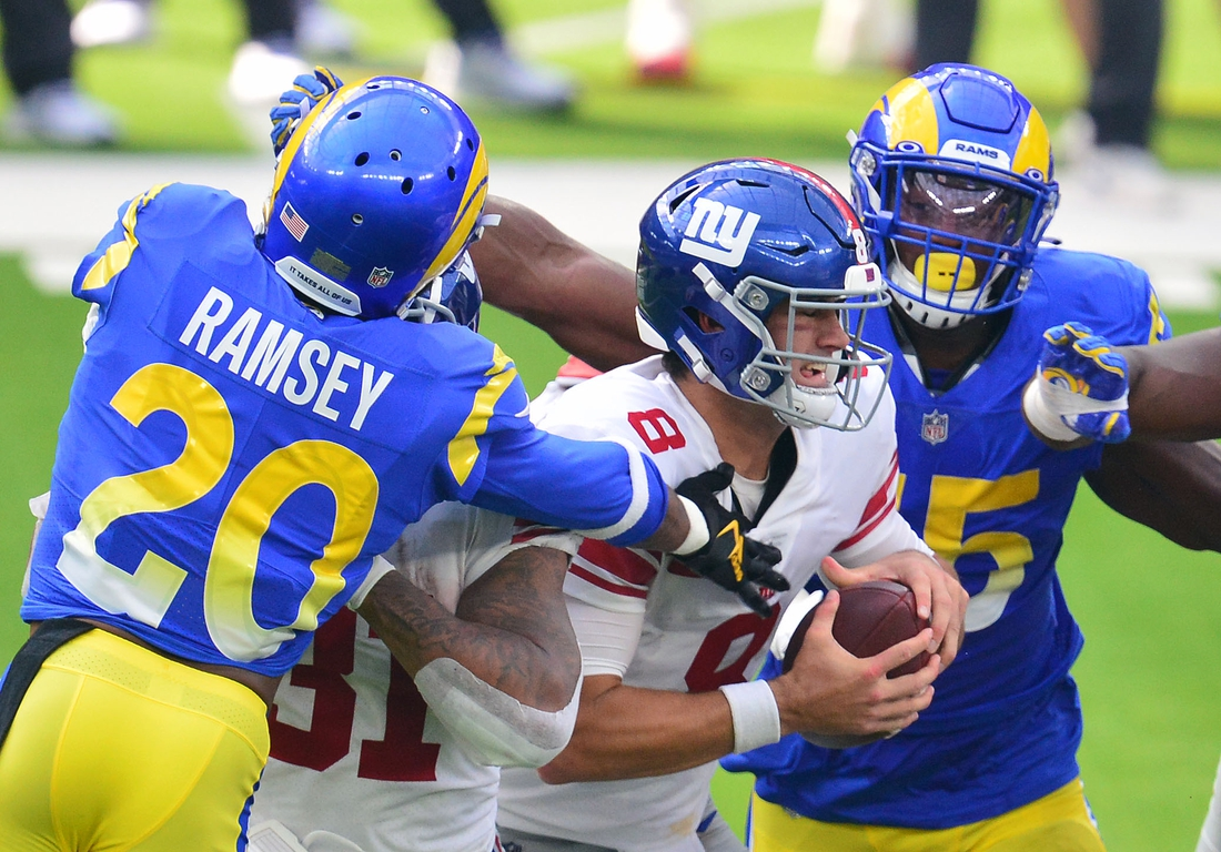 Oct 4, 2020; Inglewood, California, USA; New York Giants quarterback Daniel Jones (8) is brought down by Los Angeles Rams cornerback Jalen Ramsey (20) and center Coleman Shelton (65) during the first half at SoFi Stadium. Mandatory Credit: Gary A. Vasquez-USA TODAY Sports