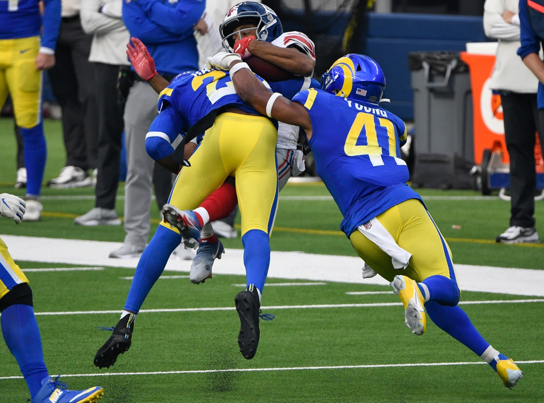 Oct 4, 2020; Inglewood, California, USA; Los Angeles Rams cornerback Jalen Ramsey (20) makes a leaping tackle to stop New York Giants wide receiver Golden Tate (15) during the second half at SoFi Stadium. Rifghrt is Los Angeles Rams outside linebacker Kenny Young (41). Mandatory Credit: Robert Hanashiro-USA TODAY Sports